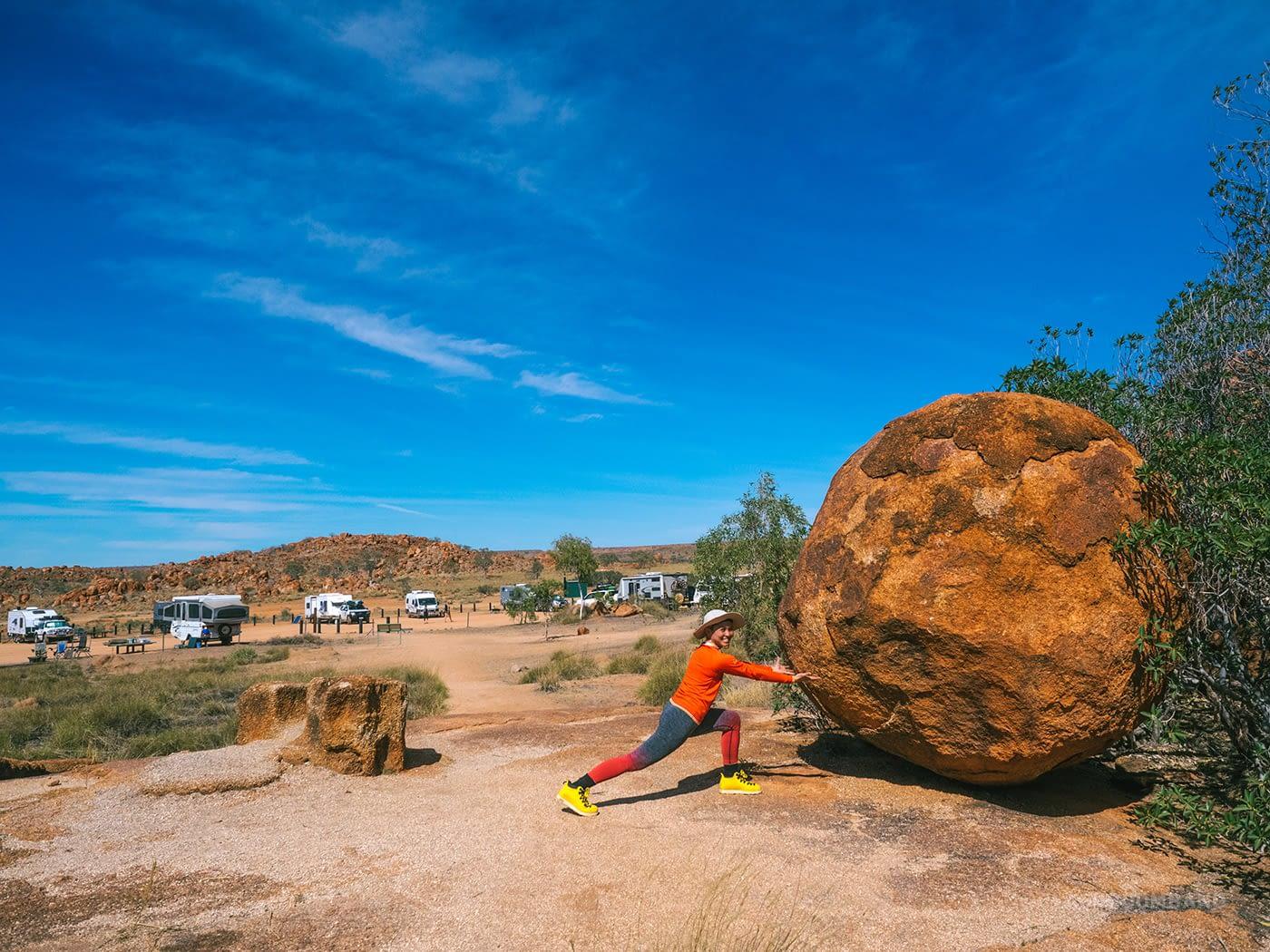 NT Australia - Karlu Karlu - E posing as if she's trying to move the boulder